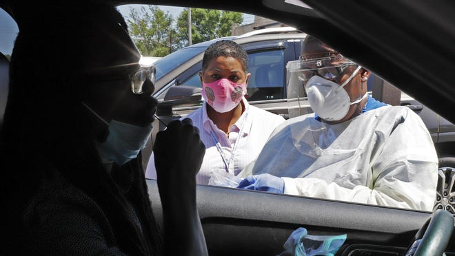 Kiva A. Fisher-Green, center, watches as nurse Ruth John, right, takes a sample from Walter Lewis for a COVID-19 test in the driveway of the Alma Illery Medical Center in the Homewood neighborhood of Pittsburgh on Monday, July 20, 2020. The state's Department of Health is hiring 1,000 additional contract tracers to bolster the state's efforts to contain coronavirus outbreaks by quickly notifying people who might have been exposed.