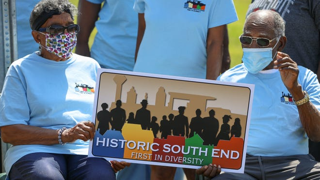 Flora Peoples (left) and Henry Brown, both residents of Kent's Historic South End, hold a replica of the new sign that denotes the area's historical significance on July 3.