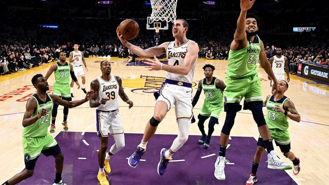 Los Angeles Lakers' Alex Caruso (4) goes to basket under pressure from Minnesota Timberwolves' Karl-Anthony Towns (32) during the second half of an NBA basketball game, Sunday, Dec. 8, 2019, in Los Angeles.