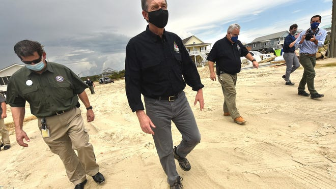 N.C. Gov. Roy Cooper tours West Beach Drive in Oak Island Thursday, Aug. 6, two day after Hurricane Isaias came ashore.