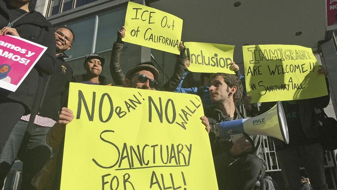 FILE - In this April 14, 2017 file photo, protesters hold up signs outside a courthouse in San Francisco. The Supreme Court on Monday, June 15, 2020 rejected the Trump administration's bid to throw out a California immigrant-sanctuary law that limits local police cooperation with federal immigration authorities.