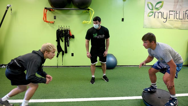 Louisville wrestlers Dan Adams (left) and Davin Rhoads (right) work with trainer Dylan Wasosky at My Fit Life in Louisville Monday, June 08, 2020.