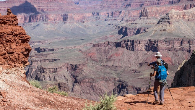 Hikers walk by the edge of the cliffs of the Grand Canyon in this May 15, 2019, file photo.