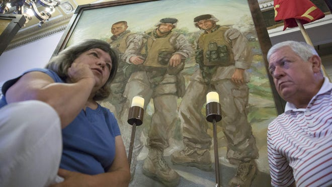 In this file photo from July 28, 2015, Pat Murray, left, and Ken Kreuter sit beneath a portrait of their son Marine Sgt. David Kreuter, top right, at the traveling Eyes of Freedom Lima Company Memorial then displayed at the Cincinnati Masonic Center. Kreuter was one of 14 Marines from Ohio-based Lima Company who were killed by an IED explosion in Iraq 15 years ago.