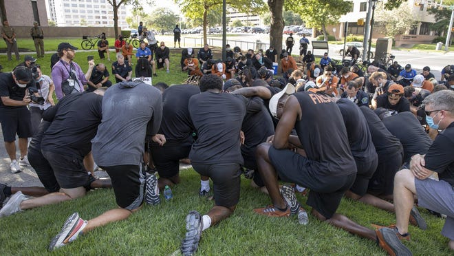 University of Texas football players kneel in silence for nine minutes at the end of a June 4 team march to the Capitol to protest the killing of George Floyd.