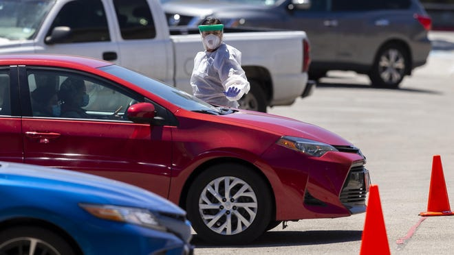 With more than 25 cars in line, a medical professional directs traffic at a coronavirus testing site outside CommUnityCare in Central Austin on Thursday.