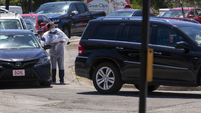 A medical professional speaks Thursday with a driver at a coronavirus testing site in Central Austin outside CommUnityCare, where more than 25 cars were in line.