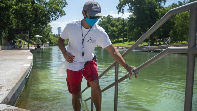 In this file photo, lifeguard Thomas Dinh cleans parts of Barton Springs Pool in Austin on June 9, 2020.