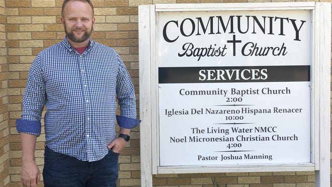 Pastor Joshua Manning poses outside his Community Baptist Church in Noel, Mo. The town of 1,800 residents has been hit hard by the coronavirus.