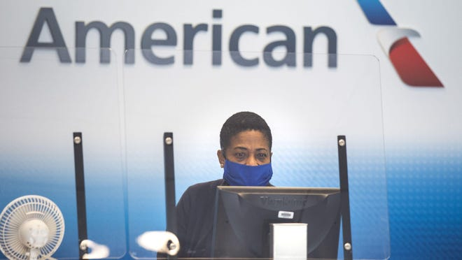 An American Airlines employee waits to help the next passenger check luggage in Terminal A at DFW International Airport in Irving, Texas, on Sunday, July 26, 2020.