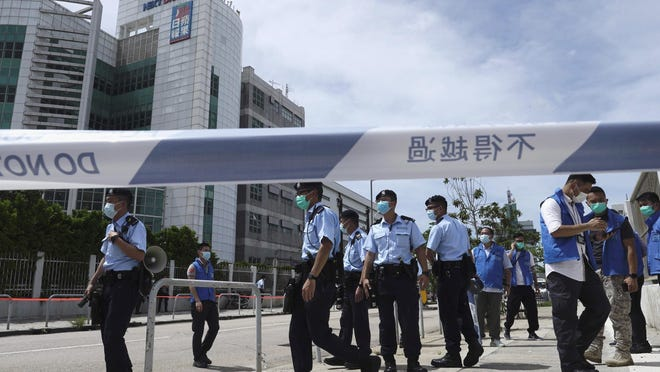 Police officers stand guard outside Apple Daily headquarters as Hong Kong media tycoon Jimmy Lai, who founded local newspaper Apple Daily, is arrested by police officers at his home in Hong Kong, Monday, Aug. 10, 2020. Hong Kong police arrested Lai and raided the publisher's headquarters Monday in the highest-profile use yet of the new national security law Beijing imposed on the city after protests last year.