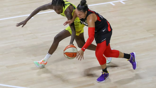 Las Vegas Aces' Kayla McBride, right, has the ball knocked away by Seattle Storm's Natasha Howard during the second half of a WNBA basketball game Saturday, Aug. 22, 2020, in Bradenton, Fla.
