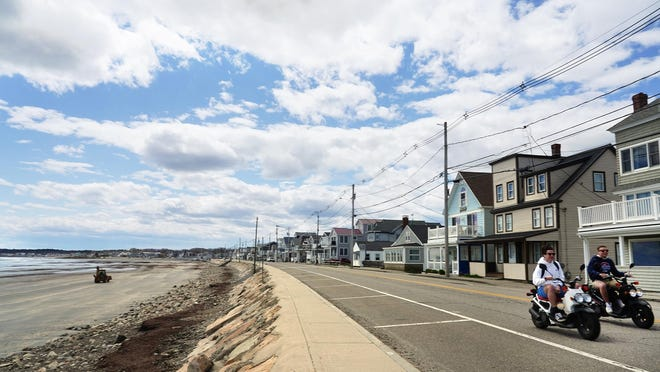 People on scooters ride along a quiet Long Beach Ave in York on a sunny day at the beach in May 2020.