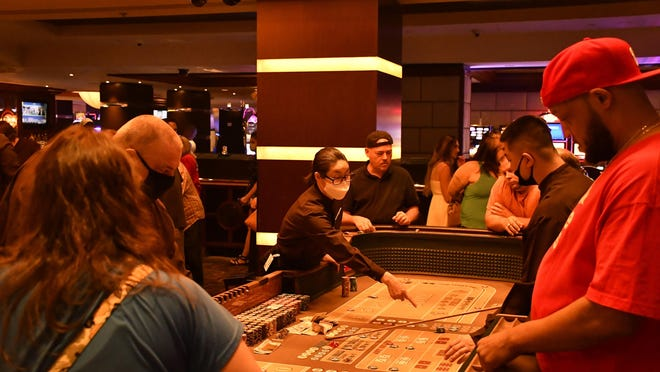 Gaming tables at the Golden Nugget are busy within minutes of the Las Vegas casino's reopening at 12:01 a.m. June 4. Workers are required to wear masks; guests are encouraged but not required.
