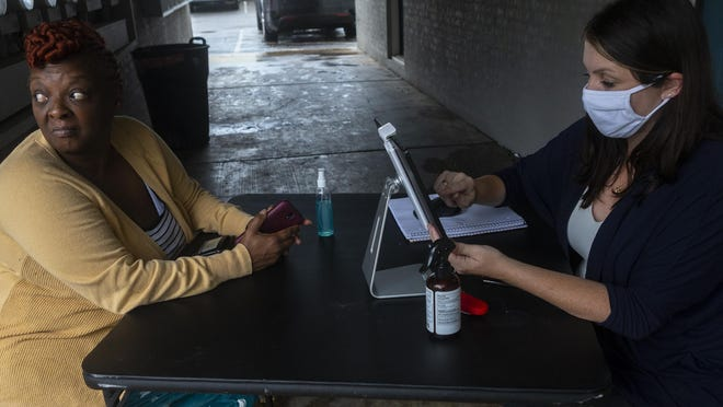 Lyndsay Hanes of Metric Property Management Company, helps apartment resident Kathy King apply for rent assistance from the city of Austin last year.