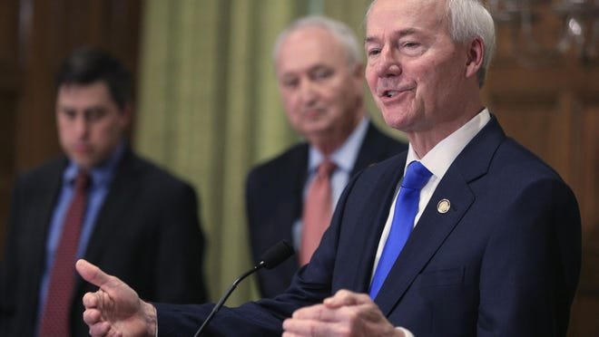 Hutchinson says he's not ready to further ease restrictions on businesses as the number of coronavirus cases in the state continue to spike. Hutchinson on Thursday said Arkansas' plans to further lift restrictions remains on pause after neighboring Texas halted its aggressive reopening of businesses.