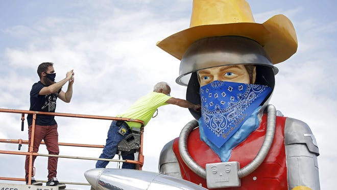Artist Adam Carnes (left) and Gary Coulson place a mask on Buck Atom, the mascot of Buck Atom's Cosmic Curious Route 66 on Friday in Tulsa. The city now has a mask mandate to protect against the spread of COVID-19.