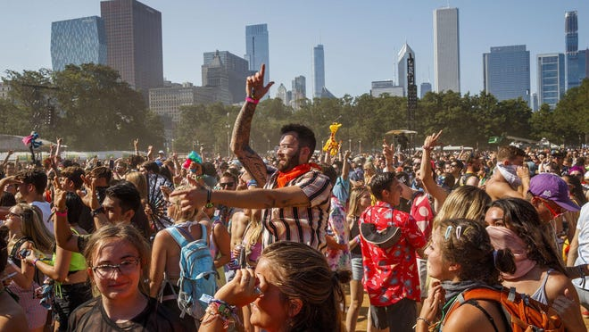 In this file photo, attendees dance at the Perry's stage during the last day of the 2019 Lollapalooza Music Festival in Grant Park Sunday Aug., 4, 2019, in Chicago. A free virtual version of Lollapalooza will take place on YouTube over the same weekend, July 30-Aug. 2.