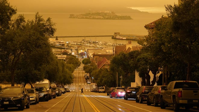 Under darkened skies from wildfire smoke, a man crosses Hyde Street with Alcatraz Island and Fisherman's Wharf in the background Wednesday, Sept. 9, 2020, in San Francisco. People from San Francisco to Seattle woke Wednesday to hazy clouds of smoke lingering in the air, darkening the sky to an eerie orange glow that kept street lights illuminated into midday, all thanks to dozens of wildfires throughout the West. The picture was taken in the middle of the day at 12:29 p.m.