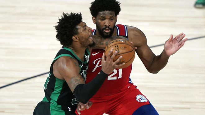 The Celtics' Marcus Smart, left, drives toward the basket as the 76ers' Joel Embiid defends during last Monday's playoff game in Lake Buena Vista, Fla. After a great start to the resumed season,  Smart has struggled offensively since.