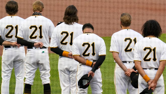 The Pittsburgh Pirates, all wearing Roberto Clemente's No. 21 for Roberto Clemente Day, watch a tribute to the Hall of Fame right fielder before the team's game against the White Sox Wednesday in Pittsburgh.
