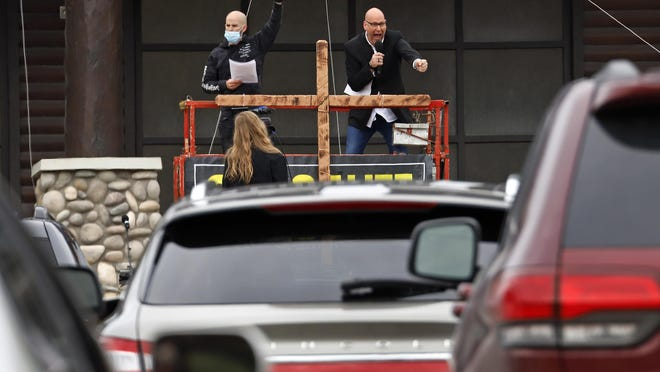 Paster Bruce Schafer, top right, preaches from a scissor lift during the first of two drive-in Easter services held by Grace Life Church in a parking lot in Monroeville, Pa., on April 12. The principle of religious freedom is important to most Americans. But as President Donald Trump touts his support for it during his reelection bid, there are notable fault lines among people of different faiths and political ideologies over what it truly means.