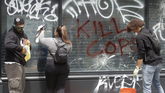 People with OccupyLove WorldWide clean graffiti off of windows in Oakland, Calif., Sunday, May 31, 2020, after protests over the Memorial Day death of George Floyd. Floyd was a black man who was killed in police custody in Minneapolis on May 25. Another black man, Patrick Underwood, who was a security officer at the Oakland federal courthouse who was protecting the property, was killed in a drive-by shooting while a protest was underway nearby.