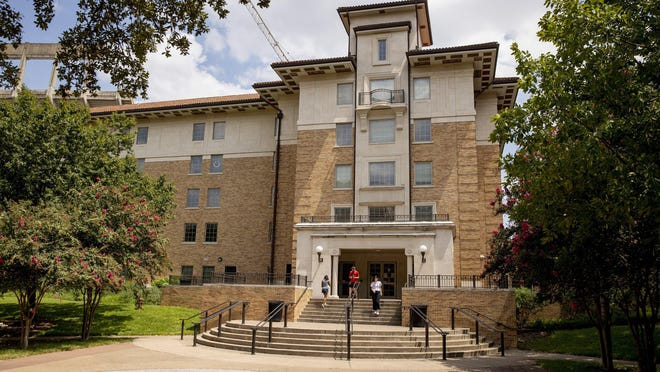 Students enter and exit the San Jacinto Residence Hall at the University of Texas on Monday. A resident of the dorm has tested positive for the coronavirus.