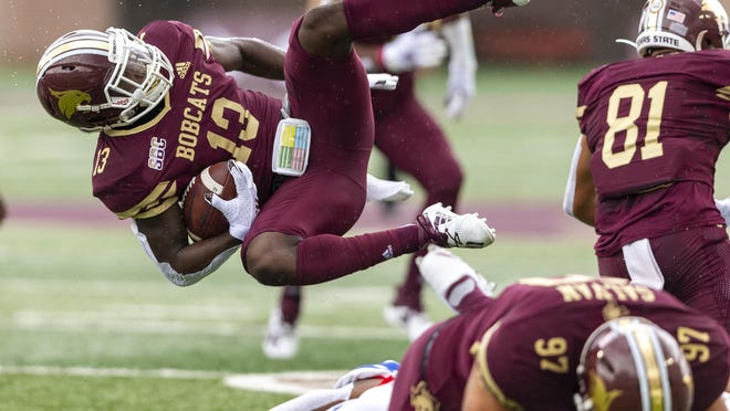 Texas State wide receiver Trevis Graham Jr. is upended by an SMU defender during Saturday's season opener in San Marcos. The Mustangs won 31-24.