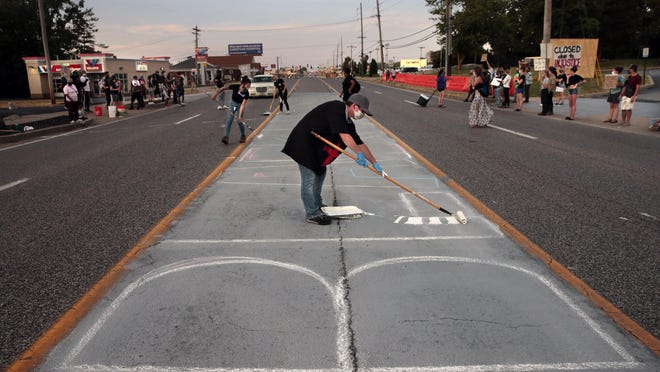 Protesters begin painting 'Black Lives Matter' Sunday on Lindbergh Boulevard in Florissant before being stopped by police. A person at the demonstration Tuesday night is recovering from a bullet wound after the rifle he was carrying discharged accidentally.