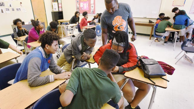 Matthew Gilbert Middle School (a middle school in Duvall County, Fla.) history teacher Dejuan Green works with students in his U.S. history class as they take a review quiz on their phones.