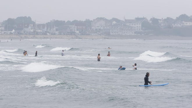 Surfers and swimmers test out the waves on Sunday at Long Sands Beach in York. On Friday, three teens were rescued by lifeguards and on Monday, Parks and Recreation employee Ryan Coite rescued a distressed diver from the water near the Nubble Light.