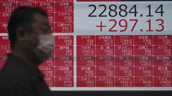 A man walks past an electronic stock board showing Japan's Nikkei 225 index at a securities firm in Tokyo Wednesday, July 15, 2020.