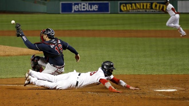 The Red Sox' Alex Verdugo slides home ahead of the tag from Braves catcher Travis d'Arnaud  on a single by Rafael Devers, right rear, during the third inning of Tuesday night's game.