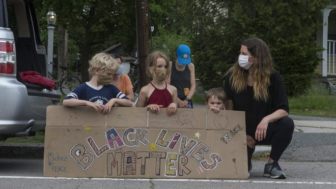 Community members stand together to protest systemic racism and police brutality for the Black Lives Matter movement in Milton on Thursday June 4, 2020.