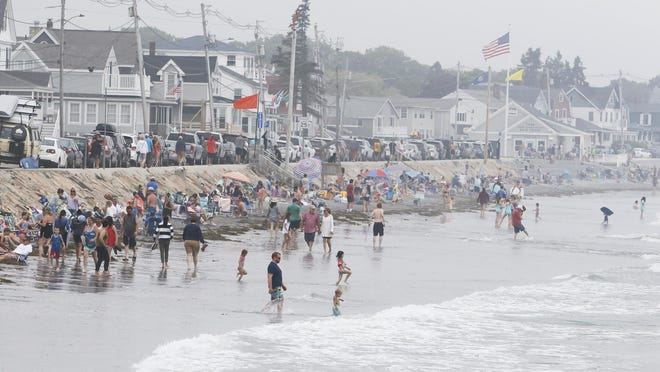 Visitors on Long Sands Beach in York at noontime Sunday, July 5. High tide occurred at about 11 a.m. both days of the holiday weekend pushing beach-goers to the beach's edge and making social distancing difficult.