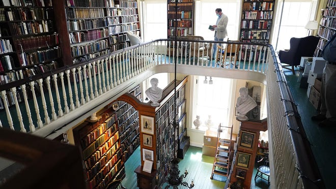 Attorney Brad Lown, president of the Portsmouth Athenæum walks around the balcony of the independent membership library, gallery, and museum in Portsmouth.