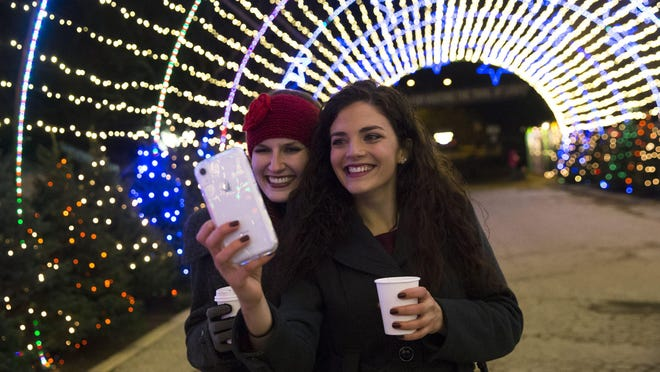 """Abigail Jurica, left, and Kaylee Harrison take a selfie together beneath the """"Starry Night"""" display during the fifth annual preview party for the Trail of Lights at Zilker Park in 2018. This year, the Trail of Lights will be drive-thru only."""