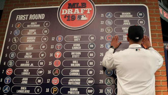 In this June 3, 2019, file photo, Daniel Espino, a right-handed pitcher from Georgia Premier Academy in Statesboro, Ga., places his name on the draft board after being selected No. 24 by the Cleveland Indians in the first round of the baseball draft in Secaucus, N.J. Baseball's amateur draft this week will look much different because of the coronavirus pandemic, and more permanent changes could be coming soon.