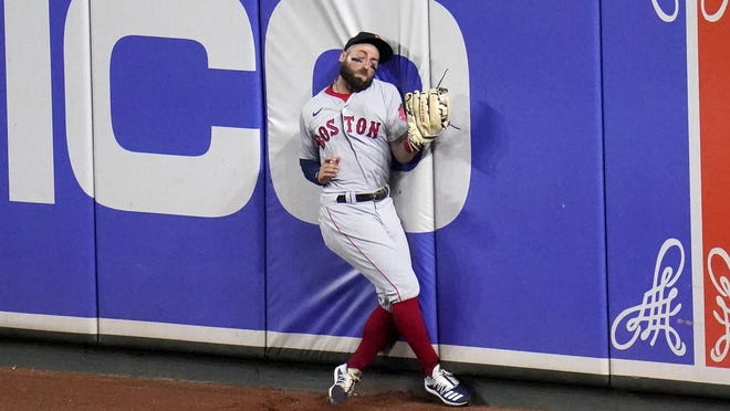 Boston Red Sox right fielder Kevin Pillar hits the wall while making a catch on a ball hit by the Baltimore Orioles' Ryan Mountcastle during the fifth inning of Saturday's game in Baltimore.