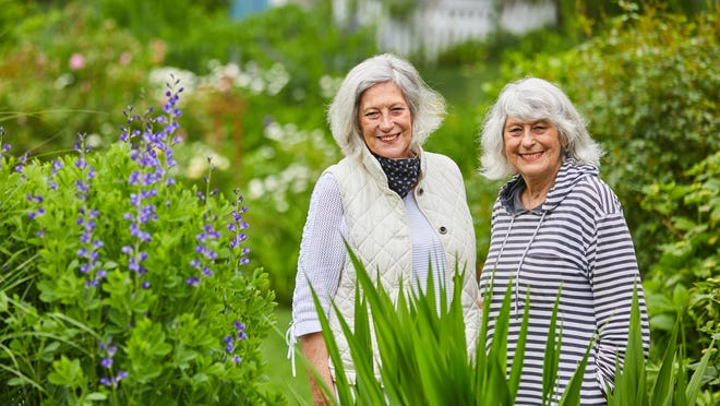 """Pamela Adam is joined by her sister Sandra Arnold in the lush garden of Little Inn on Pleasant Bay, which they've owned for 19 years. The inn, located in Orleans, opened for guests on Wednesday.  """"For months, we had nothing but cancellations. Now the phone is ringing off the hook,"""" Adam said."""