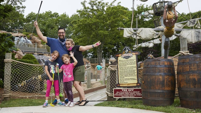 The Pires family, from left, Anjolie, David, Delilah and Monika, tee off at Pirate's Cove Adventure Golf in West Yarmouth on their first visit to Cape Cod.