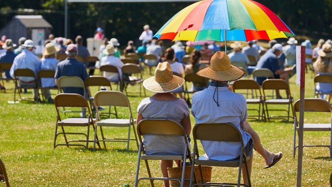 Residents use umbrellas and hats to protect themselves from the sun Saturday morning at the Orleans annual town meeting at Nauset Regional Middle School. It was the first time annual meeting was held outdoors.