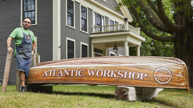 Scott Feen, owner of Atlantic Workshop in Orleans, uses his boat as a sign for his business in front of his home on Main Street. Feen is fighting one of the conditions placed on a special permit issued by the town's Zoning Board of Appeals that a sign can't be used on the property.