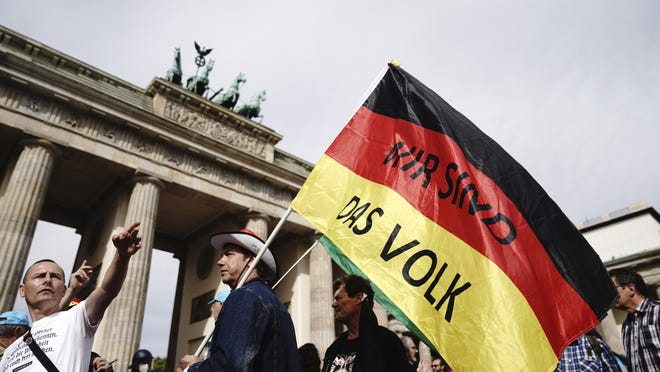 "A participant of a demonstration against the Corona measures holds a German flag with the writing ""We are the people,"" the motto of the 1989 revolution in east Germany, in Berlin Saturday."