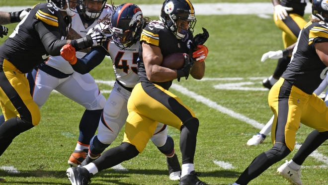 Pittsburgh Steelers running back James Conner (30) gets past Denver Broncos linebacker A.J. Johnson (45) during the first half of an NFL football game in Pittsburgh, Sunday, Sept. 20, 2020.
