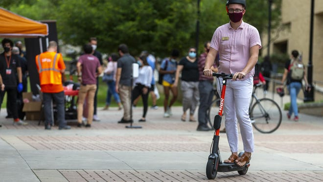 Graduate student David Eller takes a free test ride of a Spin electric scooter at Texas State University in San Marcos on Wednesday. Scooter rentals cost $1 to unlock and 29 cents for every minute of use.