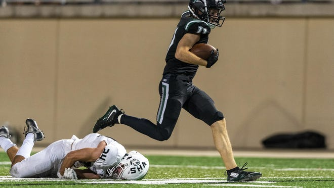 Cedar Park wide receiver Preston Scott escapes a tackle by Vandegrift defensive back Griffin Shaffer to score a touchdown during the Timberwolves' 21-7 win Friday at Gupton Stadium.