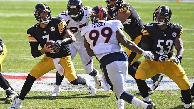 Pittsburgh quarterback Ben Roethlisberger, left, moves out of the pocket under pressure from Denver defensive end Jurrell Casey (99) and linebacker Jeremiah Attaochu (97) during the second half on Sept. 20 in Pittsburgh.
