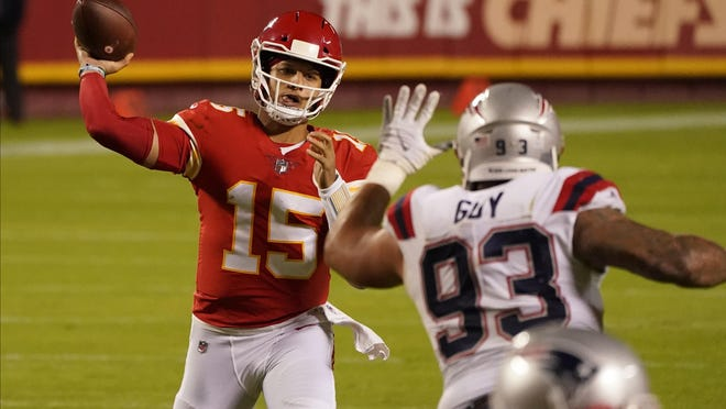 Kansas City quarterback Patrick Mahomes (15) throws as New England's  Lawrence Guy applies pressure during the second half of Monday' game.